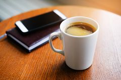 In the cafe on a wooden table there is a white mug with a cappuccino, a notebook or a diary and a mobile phone. Breakfast stock photos