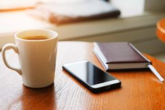 In the cafe on a wooden table there is a white mug with a cappuccino, a notebook or a diary and a mobile phone. Breakfast royalty free stock image