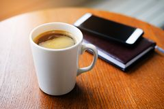 In the cafe on a wooden table there is a white mug with a cappuccino, a notebook or a diary and a mobile phone. Breakfast stock images