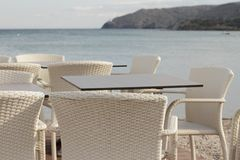 Cafe with wooden tables and cane chairs at the seaside. With the view on the sea stock image