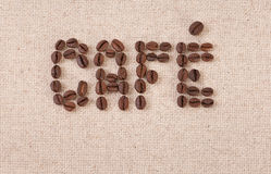 Cafe written with coffee beans on canvas. The word cafe written with coffee beans on canvas Royalty Free Stock Photography