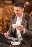 Cafe. Young attractive man on a coffee break with his laptop Royalty Free Stock Image