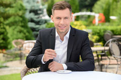 Cafe. Young businessman drinking coffee while sitting in a cafe outdoors stock photos