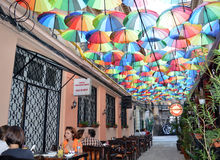 Cafes under umbrella roof in Pasagiul Victoriei. Customers at cafe under roof made from umbrellas in Bucharest, Romania royalty free stock photos