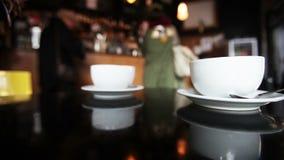 A cafetaria, clientes no contador é visível no borrão do fundo filme