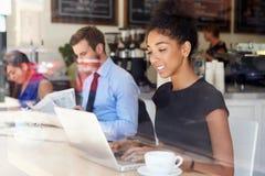Cafetaria de Using Laptop In da mulher de negócios Fotos de Stock