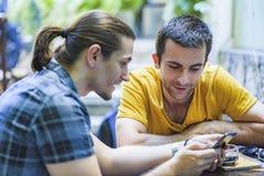 Cafetería al aire libre, dos amigos masculinos imágenes de archivo libres de regalías