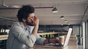 Cafetería cansada de Using Laptop In del hombre de negocios almacen de video