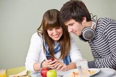 Cafetería del estudiante - par adolescente con el teléfono Imagen de archivo