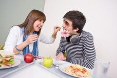 Cafetería del estudiante - par adolescente que se divierte Imágenes de archivo libres de regalías