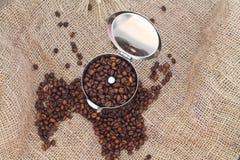 Cafetera con los granos de café foto de archivo