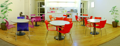 Cafeteria. A modern cafeteria with round tables and colorful chairs stock photography