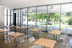 Cafeteria. Elegant empty cafeteria with wooden tables and steel chairs Stock Photography