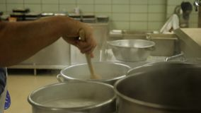 Cafeteria Cook Pours Pierogies in Boiling Pot. 10172 A cafeteria cook dumps freshly-made pierogies in a boiling pot on an industrial stovetop stock video footage