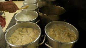 Cafeteria Cook Stirs Boiling Pots on Stove. 10171 A cafeteria cook stirs pierogies boiling in large pots on an industrial stovetop stock video