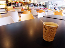 Cafeteria table with cup of hot coffee