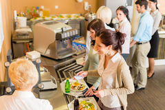 At the cafeteria woman pay bill. Cafeteria women pay at cashier hold serving tray fresh food stock images