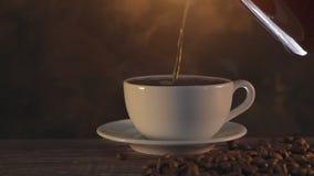 Caffè aromatico di cottura a vapore caldo fresco che è versato in una tazza bianca archivi video