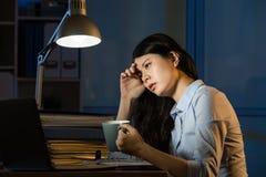 Caffè asiatico della bevanda della donna di affari che rinfresca lavorando fuori orario La fotografia stock