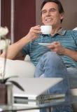 Caffè bevente alla domenica mattina. Uomo maturo allegro che si siede o fotografia stock