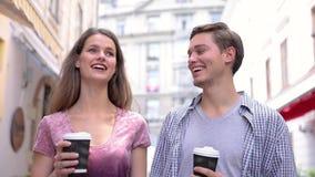 Caffè bevente dei giovani e camminare alla via della città video d archivio