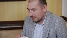 Caffè bevente del giovane mentre sedendosi in una sedia e parlando online in un computer portatile archivi video