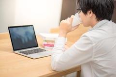 Caffè bevente del giovane studente universitario asiatico dell'uomo Fotografia Stock