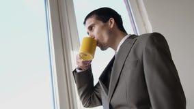 Caffè bevente del giovane uomo d'affari bello ed ammirare la finestra facente una pausa di vista in ufficio 3840x2160, 4K video d archivio