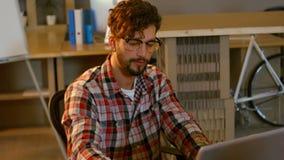 Caffè bevente del grafico mentre lavorando al computer portatile archivi video