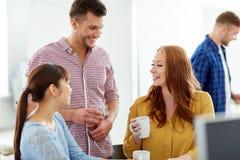 Caffè bevente del gruppo creativo felice all'ufficio Fotografia Stock