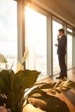 Caffè bevente del riuscito uomo d'affari, guardante attraverso l'ufficio w fotografie stock libere da diritti