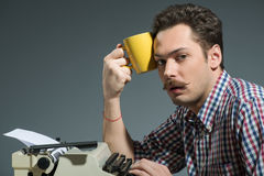 Caffè bevente dell'autore alla macchina da scrivere Fotografie Stock Libere da Diritti