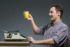 Caffè bevente dell'autore alla macchina da scrivere Immagini Stock Libere da Diritti