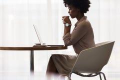 Caffè bevente dell'impiegato di concetto ed esaminare computer portatile immagini stock libere da diritti