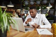 Caffè bevente dell'uomo africano delle free lance che lavora al caffè con il computer portatile Immagine Stock Libera da Diritti