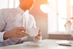 Caffè bevente dell'uomo al desktop Fotografia Stock Libera da Diritti