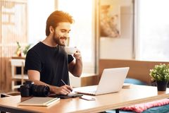 Caffè bevente dell'uomo barbuto delle free lance al computer portatile che si siede allo scrittorio fotografia stock