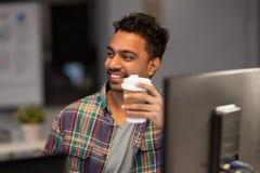 Caffè bevente dell'uomo creativo felice all'ufficio di notte fotografie stock