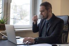 caffè bevente dell'uomo d'affari che lavora al computer portatile in ufficio che prende le note immagine stock libera da diritti