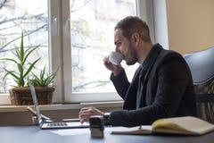 caffè bevente dell'uomo d'affari che lavora al computer portatile in ufficio che prende le note fotografia stock