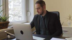 caffè bevente dell'uomo d'affari che lavora al computer portatile in ufficio che prende le note archivi video