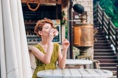 Caffè bevente della bella donna al caffè Fotografie Stock