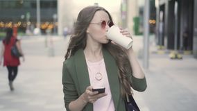 Caffè bevente della bella donna di affari da andare e praticare il surfing netto camminando in via video d archivio