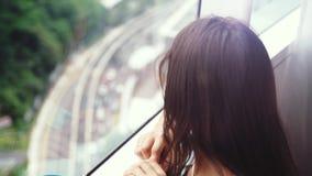 Caffè bevente della bella giovane donna castana dalla finestra panoramica con la vista di stupore della città Movimento lento 384 archivi video