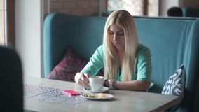 Caffè bevente della bionda ed esaminare il suo orologio archivi video