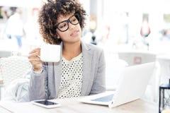 Caffè bevente della donna afroamericana elegante, lavorante Immagine Stock Libera da Diritti