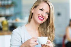 Caffè bevente della donna al caffè Fotografie Stock Libere da Diritti