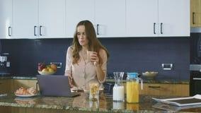 Caffè bevente della donna di affari in cucina di lusso Signora sorridente che mangia prima colazione video d archivio