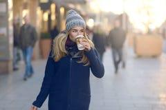 Caffè bevente della donna e camminare nella città fotografia stock libera da diritti