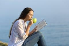 Caffè bevente della donna e leggere un libro all'aperto Immagini Stock Libere da Diritti